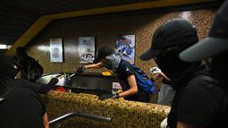 Sejumlah demonstran bertopeng merusak Stasiun MTR Wong Tai Sin di Distrik Kowloon, Hong Kong, Senin (7/10/2019). Eskalasi kerusuhan di Hong Kong semakin membesar setelah pemerintah mengeluarkan larangan demonstrasi menggunakan masker atau UU Antitopeng. (Philip FONG/AFP)