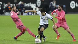 Gelandang Valencia, Lee Kang-in mengontrol bola dibayangi pemain Real Madrid pada lanjutan La Liga di Stadion Mestalla, Selasa (9/11/2020) dinihari WIB. Real Madrid kalah telak 1-4 dari tuan rumah Valencia. (AP Photo/Alberto Saiz)