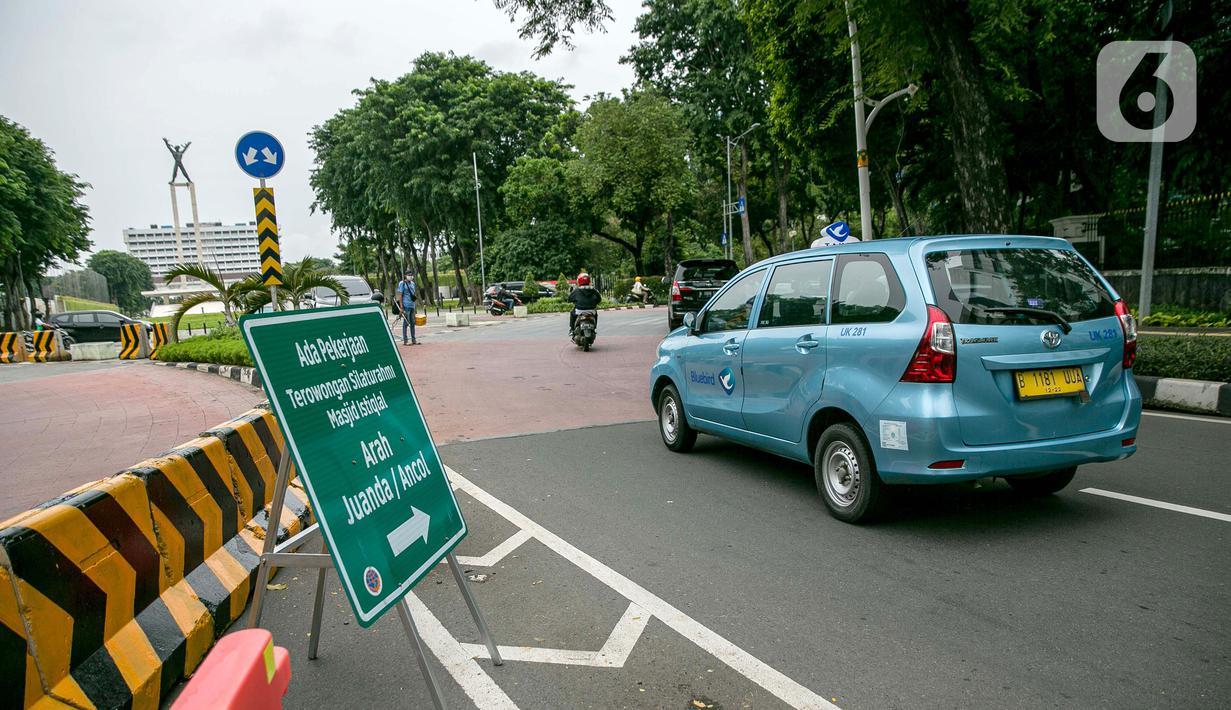Taksi melintasi rambu lalu lintas pemberitahuan pengalihan jalan di kawasan Lapangan Banteng, Jakarta, Rabu (21/1/2021). Jalan Katedral akan ditutup selama proyek pembangunan terowongan silaturahmi Masjid Istiqlal-Gereja Katedral pada 20 Januari-31 Maret 2021. (Liputan6.com/Faizal Fanani)