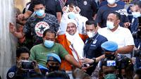 M Rizieq Shihab (tengah) mengangkat tangan saat meninggalkan gedung Ditreskrimum Polda Metro Jaya, Jakarta, Minggu dini hari (13/12/2020). Rizieq Shihab ditahan setelah menjalani pemeriksaan sebagai tersangka penghasutan dan kerumunan di tengah pandemi COVID-19. (Liputan6.com/Helmi Fithriansyah)