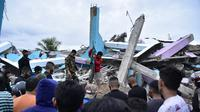 Tim penyelamat mencari korban usai gempa meruntuhkan Rumah Sakit Mitra Manakarra, Kota Mamuju, Sulawesi Barat, Indonesia, Jumat (15/1/2021). Sebanyak 20 pasien dan staf terjebak di bawah reruntuhan bangunan. (Firdaus/AFP)