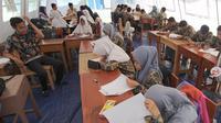 Murid SMP dan SMA Sekolah Khusus (SKh) Assalam 01 melaksanakan ujian di tenda darurat halaman SKh Assalam 02, Ciater, Serpong, Tangerang Selatan, Selasa (3/12/2019). Ujian diikuti murid penyandang tunarungu, tunawicara, dan tunagrahita tingkat SD hingga SMA. (merdeka.com/Arie Basuki)