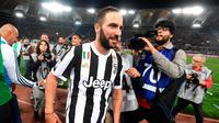 Striker Juventus, Gonzalo Higuain merayakan gelar juara Serie A Italia usai pertandingan melawan AS Roma pada lanjutan Liga Serie A Italia di stadion Olimpiade, (13/5). Ini merupakan gelar ketujuh beruntun Juventus. (AP Photo/Claudio Peri)