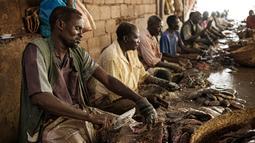 Sejumlah pedagang memotong ikan di sebuah pasar ikan di dekat Sungai Nil, di kota kembar Khartoum, Omdurman (24/6/2019). Kota Omdurman didirikan pada tahun 1884. (AFP Photo/Yasuyoshi Chiba)
