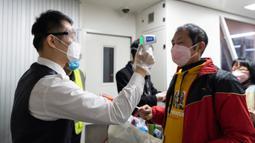 Seorang staf mengukur suhu tubuh penumpang  di Bandara Liuji di Kota Xiangyang, Provinsi Hubei, China (29/3/2020). Layanan penerbangan penumpang domestik kembali beroperasi di Hubei, wilayah yang sempat terdampak COVID-19, kecuali layanan di Bandara Internasional Tianhe Wuhan. (Xinhua/Xie Jianfei)