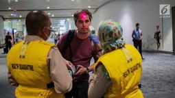Petugas Kesehatan Karantina Bandara (KKB) memeriksa suhu badan penumpang yang baru mendarat di Terminal 3 Bandara Soetta, Tangerang, Rabu (15/5/2019). Pemeriksaan ini setelah ditemukan kasus wisatawan Afrika yang mengidap cacar monyet di Singapura beberapa waktu lalu. (Liputan6.com/Faizal Fanani)