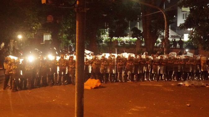 Petugas kepolisian dari Polrestabes Bandung membentuk formasi dalam rangka membubarkan aksi demonstrasi menolak omnibus law UU Cipta Kerja yang berakhir ricuh dan melewati batas waktu unjuk rasa di depan Gedung DPRD Jawa Barat, Selasa (6/10/2020). (Liputan6.com/Huyogo Simbolon)