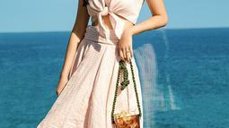 Inspirasi casual dress pantai ala liburan Raline Shah di Malibu, California. Tampil elegan dengan balutan dress warna cream, sneakers putih dan tas gelasnya (Liputan6.com/IG/ralineshah)