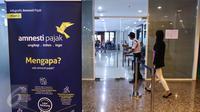 Sebuah banner terpasang di depan pintu masuk kantor pusat Ditjen Pajak, Jakarta, Minggu (25/9). Mendekati hari akhir periode pertama, Kantor Pajak membuka pendaftaran pada akhir pekan khusus melayani calon peserta tax amnesty. (Liputan6.com/Fery Pradolo)