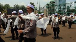 Personel Brimob yang tergabung dalam Pasukan Dzikir Asmaul Husna mengenakan sorban bersiap menjalankan salat di depan Gedung MPR/DPR, Senayan, Jakarta, Selasa (24/10). (Liputan6.com/JohanTallo)