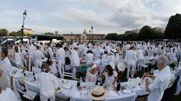 "Orang-orang berpakaian putih berkumpul bersiap untuk makan malam bersama atau ""Diner en Blanc"" yang ke-30 di Paris, Prancis (3/6). Tempat dilaksanakannya acara ini akan dirahasiakan oleh penyelenggara hingga 2-1 jam sebelum dimulai. (AFP/Francois Guillot)"