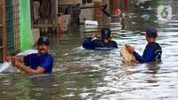 Petugas Sudin Sumber Daya Air (SDA) memunguti sampah-sampah yang tergenang saat banjir di kawasan Kampung Melayu Kecil, Bukit Duri, Jakarta, Selasa (25/2/2020). Banjir tersebut akibat luapan sungai Ciliwung. (merdeka.com/magang/ Muhammad Fayyadh)
