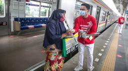 Petugas KAI Commuter (kanan) memberikan bunga dan healthy kit kepada perempuan pengguna KRL di Stasiun Jatinegara, Jakarta, Selasa (22/12/2020). Kegiatan tersebut dalam rangka memperingati Hari Ibu yang jatuh setiap tanggal 22 Desember. (Liputan6.com/Faizal Fanani)