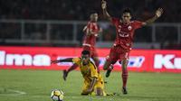 Gelandang Bhayangkara FC, Vendry Mofu, dijatuhkan bek Persija Jakarta, Dany Saputra, pada laga Liga 1 di SUGBK, Jakarta, Jumat (23/3/2018). Kedua klub bermain imbang 0-0. (Bola.com/Vitalis Yogi Trisna)