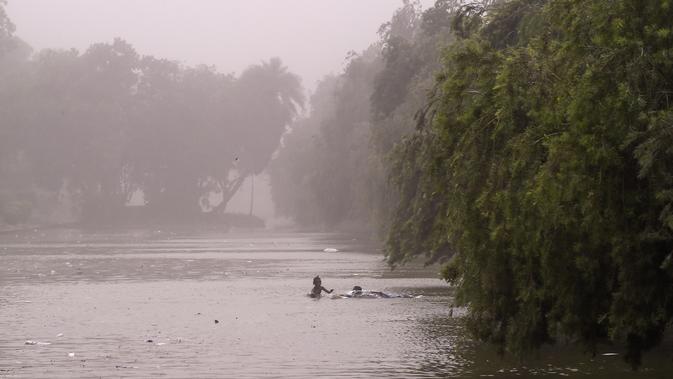 Anak-anak berenang di kolam saat badai debu menerjang New Delhi, India, Rabu (2/5). Badai terjadi di Negara Bagian Uttar Pradesh dan Rajasthan. (CHANDAN KHANNA/AFP)
