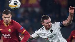 Striker AS Roma, Edin Dzeko, berebut bola dengan bek Wolfsberg, Michael Sollbauer, pada laga Liga Europa di Stadion Olimpico, Roma, Rabu (12/12). Kedua klub bermain imbang 2-2. (AFP/Filippo Monteforte)