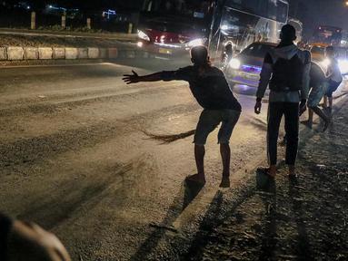 Sejumlah penyapu koin kali Sewo menunggu uang yang dilemparkan oleh pengguna jalan yang melintasi Jembatan Sewo, Kabupaten Indramayu, Jawa Barat, Minggu (2/7). (Liputan6.com/Faizal Fanani)