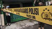 Petugas kepolisian saat memasang garis batas polisi sebelum berlangsungnya pembongkaran makam di kawasan Buaran, Jakarta Timur, Senin (24/5/2021). Nantinya pihak RSCM akan melakukan tiga penelitian dalam autopsi, yakni Pantologi Klinis, Pantologi Anatomi, dan Pantologi Makrofis Mikrofis. (merdeka.co