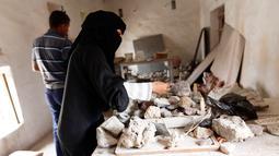 Seorang wanita bernama Safa al-Faqih memilih batu mulia yang masih mentah untuk dijadikan perhiasan dan batu cincin di tempat kerajinan di Sanaa, Yaman (18/4). (AFP/Mohammed Huwais)