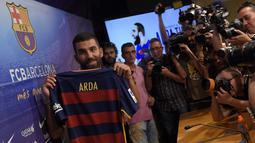 Pemain asal Turki, Arda Turan bergabung dengan Barcelona dari Atletico Madrid dengan harga  60 juta euro. (AFP Photo/Lluis Gene)