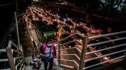 Warga menaiki JPO di tengah kepadatan lalu lintas di Manila, Filipina (3/8/2020). Kemacetan terjadi ketika orang-orang bergegas keluar dari Metro Manila beberapa jam sebelum pemerintah memberlakukan lockdown di kawasan itu akibat lonjakan kasus penyakit Covid-19. (Xinhua/Rouelle Umali)