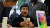 Seorang anak bermain fitur animoji iPhone X di toko Apple Union Square di San Francisco (3/11). iPhone X juga memiliki fitur terbaru Face ID yang berfungsi mendeteksi dan mengenali wajah pemilik sebagai kunci membuka perangkat. (AP Photo/Eric Risberg)