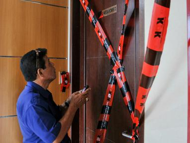 Seorang pria saat berada di depan pintu ruangan Ketua Komisi D DPRD DKI Jakarta, Mohammad Sanusi yang disegel oleh KPK, Jakarta, Jumat (1/4). Sebanyak 4 ruangan di gedung DPRD DKI Jakarta disegel oleh KPK terkait OTT. (Liputan6.com/Yoppy Renato)
