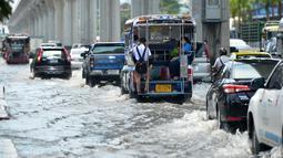 Sejumlah kendaraan melaju di sebuah jalan yang terendam banjir pascahujan lebat di Bangkok, Thailand (31/8/2020). (Xinhua/Rachen Sageamsak)
