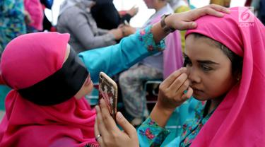 Aksi peserta saat merias wajah dengan mata tertutup di Kantor Balai Kota Tangerang Selatan, Banten, Jumat (27/4). Perlombaan ini diikuti oleh 400 peserta. (Merdeka.com/Arie Basuki)