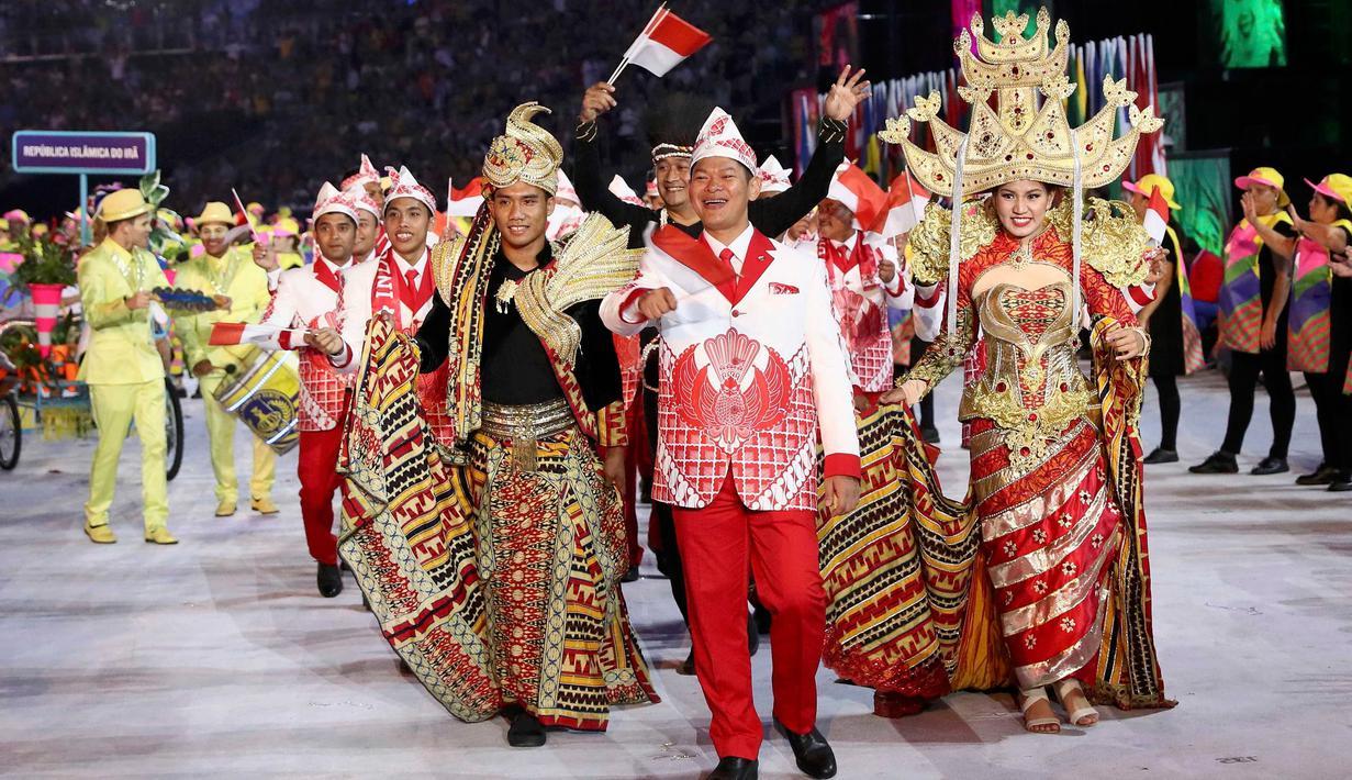 Kontingen atlet Indonesia saat mengikuti parade upacara pembukaan Olimpiade 2016 di Stadion Maracana, Rio de Janeiro, Brasil (5/8). Kostum kontingen Indonesia yang memadukan budaya Bali, Lampung, dan Papua.( REUTERS/Stefan Wermuth)