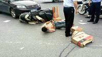 Tergeletak setelah ditabrak mobil, pria ini malah asyik main game di ponsel.