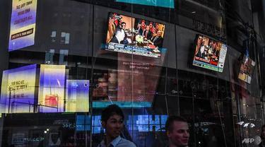 Layar televisi di New York Times Square menayangkan pertemuan bersejarah Donald Trump di Singapura. (AFP)