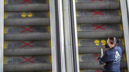 Seorang pekerja menggunakan eskalator di Bandara Internasional El Dorado, Bogota, Kolombia, Senin (31/8/2020). Presiden Kolombia Ivan Duque mengizinkan lebih banyak penerbangan domestik mulai September. (Juan BARRETO/AFP)