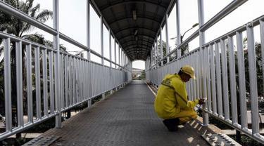 Petugas Dinas Bina Marga DKI Jakarta mengecat jembatan penyeberangan orang (JPO) di Jalan Daan Mogot, Jakarta Barat, Rabu (7/8/2019). Pengecatan ini bagian dari perawatan fasilitas umum agar masyarakat bisa menggunakan JPO dengan baik. (Liputan6.com/JohanTallo)