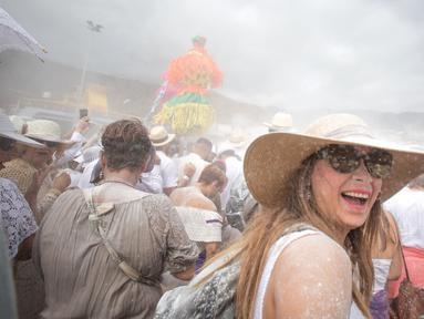 Orang-orang yang berselimut bedak ambil bagian dalam karnaval jalanan 'Los Indianos' di Santa Cruz de la Palma, Spanyol, Senin (4/3). Karnaval ini  bagian dari rangkaian acara yang diadakan sejak Januari hingga Februari tiap tahunnya. (DESIREE MARTIN/AFP)