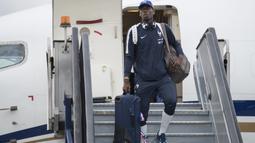 Gaya Paul Pogba menenteng koper saat tiba di Sheremetyevo international airport, Moskow, Rusia, (10/6/2018). Pada laga perdana Prancis akan melawan Australia. (AP/Pavel Golovkin)