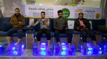 Warga Palestina merendam kaki mereka dalam akuarium berisi ikan di sebuah kafe di Kota Gaza, Palestina, Rabu (26/12/2018). Pemilik kafe mengatakan bisnisnya sedang booming setelah meluncurkan layanan pedikur ikan. (AP Photo/Khalil Hamra)