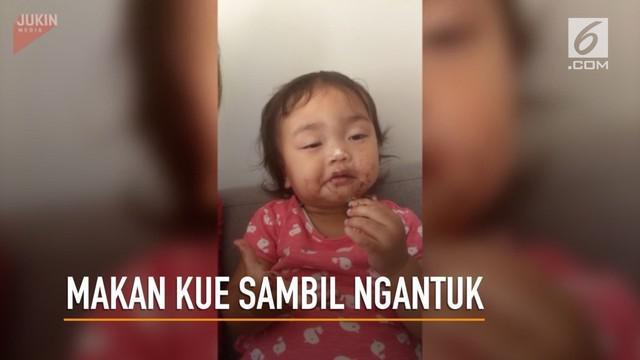 Seorang gadis kecil tetap menikmati kue yang diberikan ibunya walau sedang mengantuk berat.