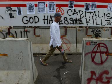 Pejalan kaki melintas dekat aksi vandalisme yang mewarnai Hari Buruh Internasional atau May Day di kawasan Bundaran HI, Jakarta, Rabu (1/5/2019). Belum diketahui siapa yang melakukan aksi corat coret di fasilitas publik tersebut. (merdeka.com/Imam Buhori)