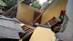 Seorang pria berdiri di antara reruntuhan rumah yang rusak akibat gempa di Lombok, NTB, Minggu (29/7). Data sementara BPBD Provinsi NTB mencatat, gempa bumi tektonik 6.4 SR itu mengakibatkan 10 orang meninggal dunia (HO/NTB DISASTER MITIGATION AGENCY/AFP)