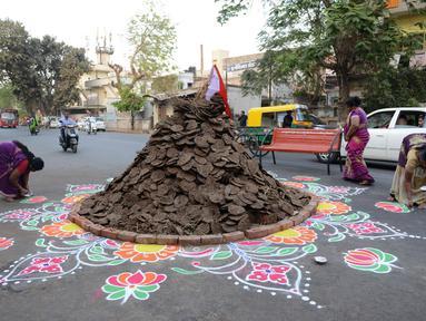 """Warga menghiasi jalan di sekitar """"Holika"""", Ahmedabad, India, Minggu (12/3). Bahan bakar Holika adalah kue yang terbuat dari kotoran sapi dan kelapa. (AFP PHOTO / SAM PANTHAKY)"""