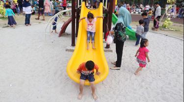 Anak-anak bermain seluncur di Lapangan Banteng, Jakarta, Minggu (14/10). Lapangan Banteng semakin ramai dikunjungi pada hari Minggu. (Liputan6.com/JohanTallo)
