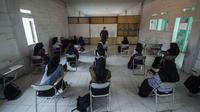 Siswa SMA menerapkan jarak sosial saat pembelajaran tatap muka di Sekolah Islam Ibnu Aqil Ibnu Sina, Soreang, Bandung, Jawa Barat, Rabu (5/8/2020). Indonesia akan mengizinkan sekolah di zona hijau COVID-19 melakukan pembelajaran tatap muka di bawah protokol kesehatan yang ketat. (Xinhua/Septianjar)