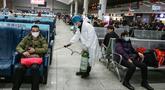 Petugas menyemprotkan cairan disinfektan di Stasiun Kereta Api Yingtan di Nanchang di Provinsi Jiangxi Tengah, China (22/1/2020). Penyemprotan dilakukan untuk mencegah virus corona menyebar ke kota lain. (AFP Photo/STR)