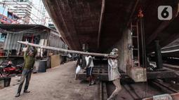 Buruh melakukan perbaikan kapal nelayan di Galangan kapal, Muara Angke, Jakarta, Minggu (23/12/2020). Dimasa pandemi Covid 19 aktivitas di galangan kapal tetap berjalan normal seperti biasa. (Liputan6.com/Angga Yuniar)
