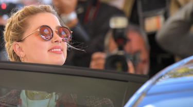 Aktris AS Amber Heard masuk ke dalam mobil saat tiba untuk menghadiri malam pembukaan Festival Film Cannes ke-72 di Prancis (13/5/2019). Mantan istri Johnny Depp ini tampil gaya dengan kaos putih, skinny jeans dan jaket multi-warna, dihiasi dengan jumbai berbulu. (AFP Photo/Loic Venance)