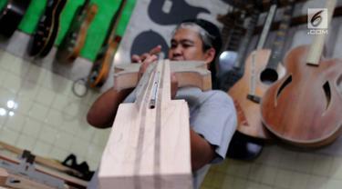 Pengrajin mengecek tingkat akurasi saat membuat gitar di Syukey Guitars, Cirendeu, Ciputat Timur (3/4). Gitar buatan tangan ini dipatok dengan harga Rp 5 juta hingga Rp 20 juta. (Merdeka.com/Arie Basuki)