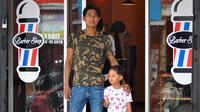 Pemain Arema, Ahmad Alfarizi, dengan putranya, Diego, di depan barbershop-nya. (Bola.com/Iwan Setiawan)