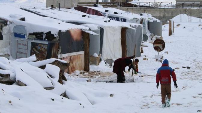 Pengungsi Suriah berjalan di salju sebuah kemah darurat di pinggiran Baalbek, Lebanon (AFP Photo)