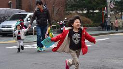 Kim Jin-Sung bersama putrinya Na-Eun dan Won-Wo pulang dari pusat penitipan anak di Seoul. Kim adalah salah satu dari meningkatnya jumlah ayah di Korea Selatan memilih istirahat dari karirnya untuk membantu membesarkan anak-anaknya. (AFP PHOTO/JU)